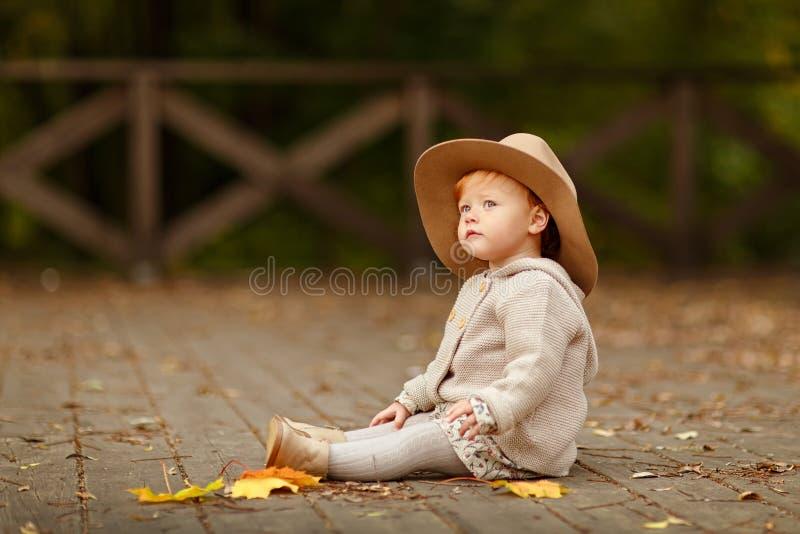 Рыжеволосый ребёнок в шляпе сидя на улице в осени стоковое изображение