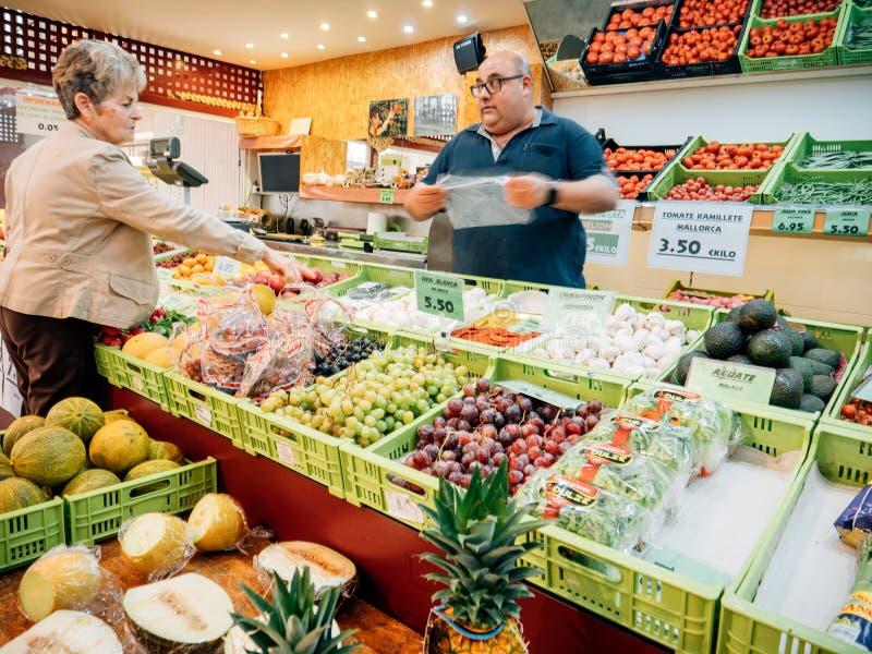 Рынок фермера фруктов и овощей испанской старшей женщины покупая стоковая фотография rf
