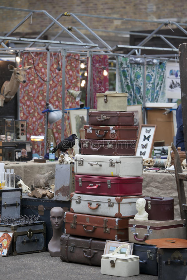 Рынок шутовства Spitalfields Продажа старых чемоданов которые лежат на одине другого Заполненная ворона на стойке на заднем плане стоковые фото