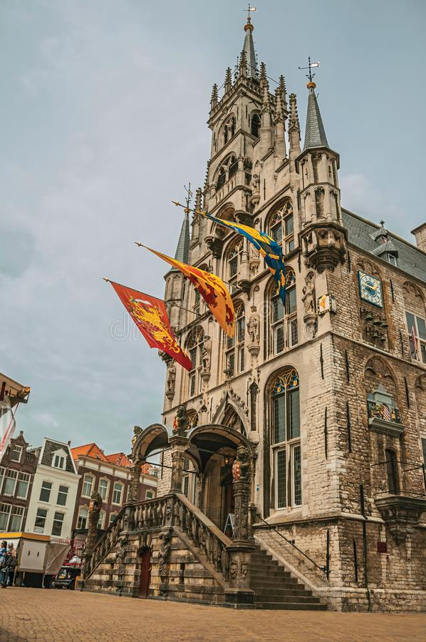 Рыночная площадь перед готическими фасадом здание муниципалитета, лестницей входа и флагами в пасмурном дне на гауда стоковые фотографии rf