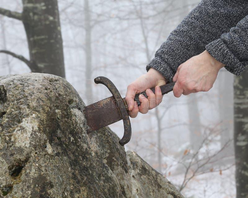 Рыцарь пробует извлечь шпагу Excalibur в камне стоковая фотография