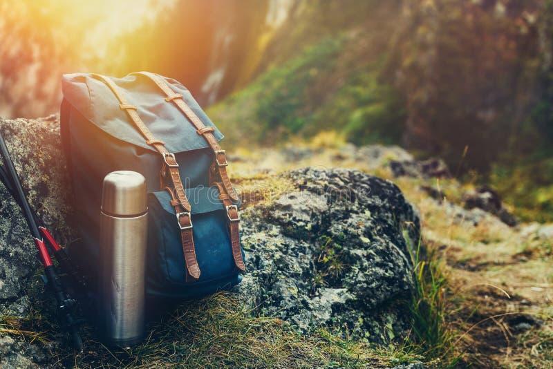 Рюкзак битника голубой, Thermos и Trekking поляки крупный план, вид спереди Туристская сумка путешественника на предпосылке утесо стоковые изображения rf