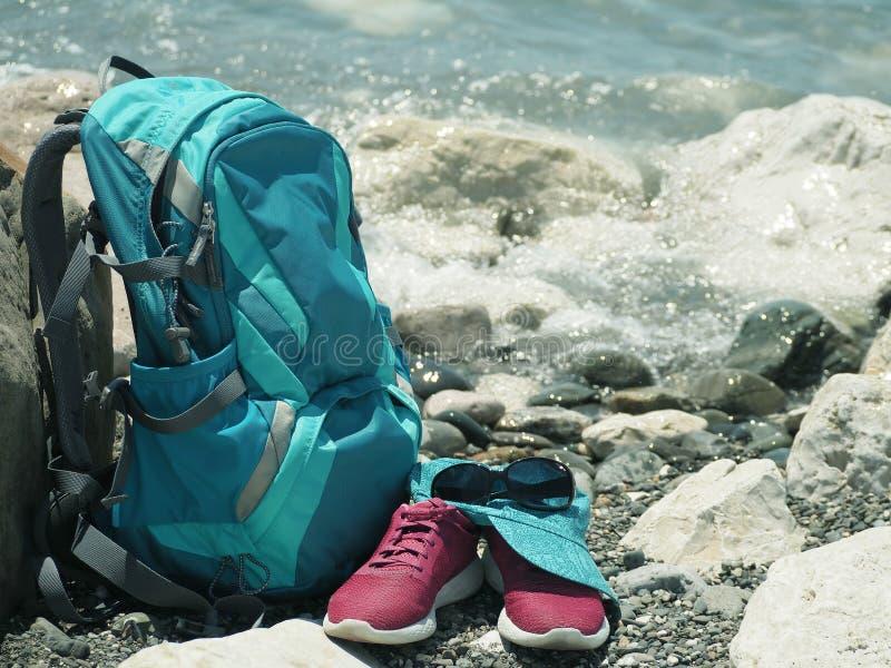 Рюкзак, ботинки бега, крышка и солнечные очки на пляже стоковая фотография