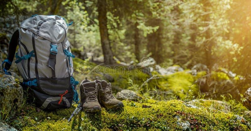 Рюкзак и пешие ботинки в лесе стоковые изображения