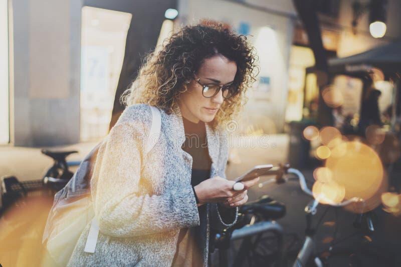 Рюкзак и стекла женского битника нося ища информацию в передвижной сети умным телефоном, во время прогулки внутри стоковое фото rf