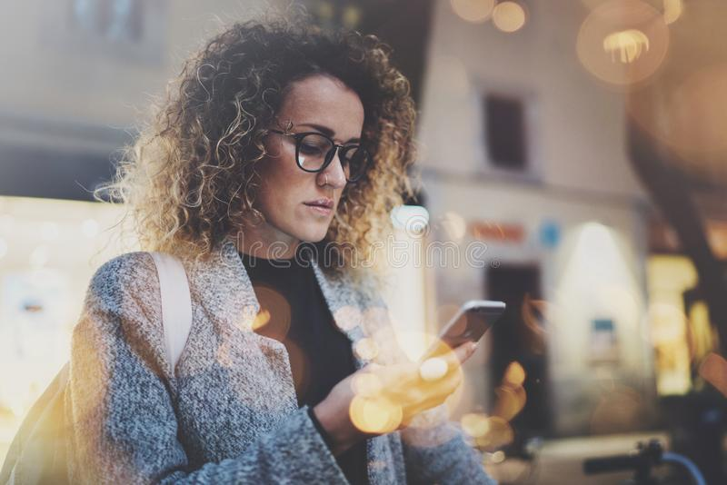 Рюкзак и стекла женского битника нося ища информацию в передвижной сети умным телефоном, во время прогулки внутри стоковое изображение rf
