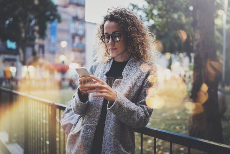 Рюкзак и стекла женского битника нося ища информацию в передвижной сети умным телефоном, во время прогулки внутри стоковые изображения