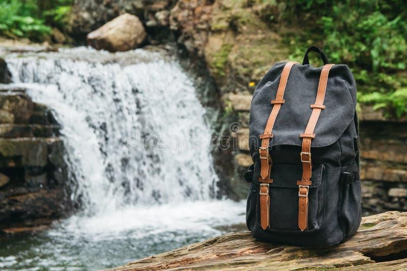 Рюкзак hiker хипстера туристский на предпосылке реки и водопада, путешественника ослабляет концепцию праздника, перемещение стоковые фото