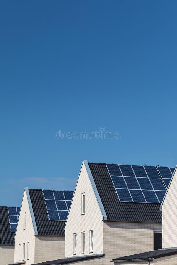 Рядок новых домов с панелями солнечных батарей на крышах стоковое фото rf