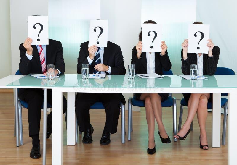 Рядок предпринимателей с вопросительными знаками стоковое изображение