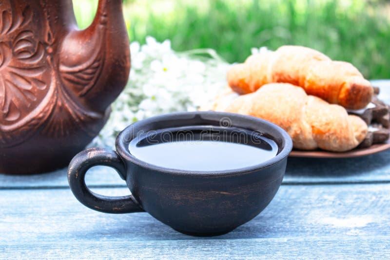 Рядом с круассанами и цветками около кувшина чашка чаю стоковая фотография