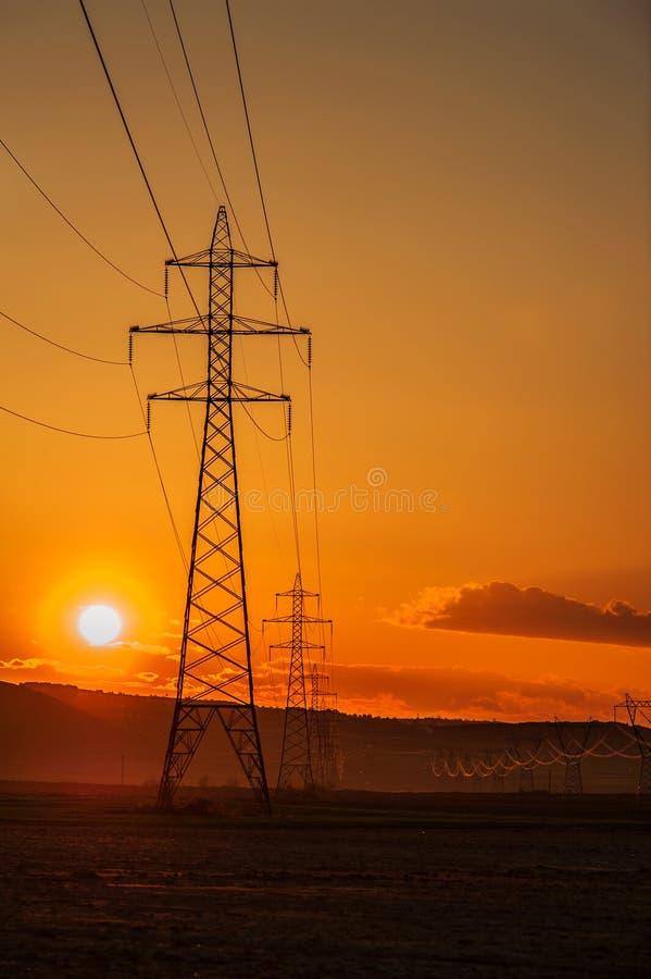 Высоковольтные столбы на заходе солнца стоковое фото