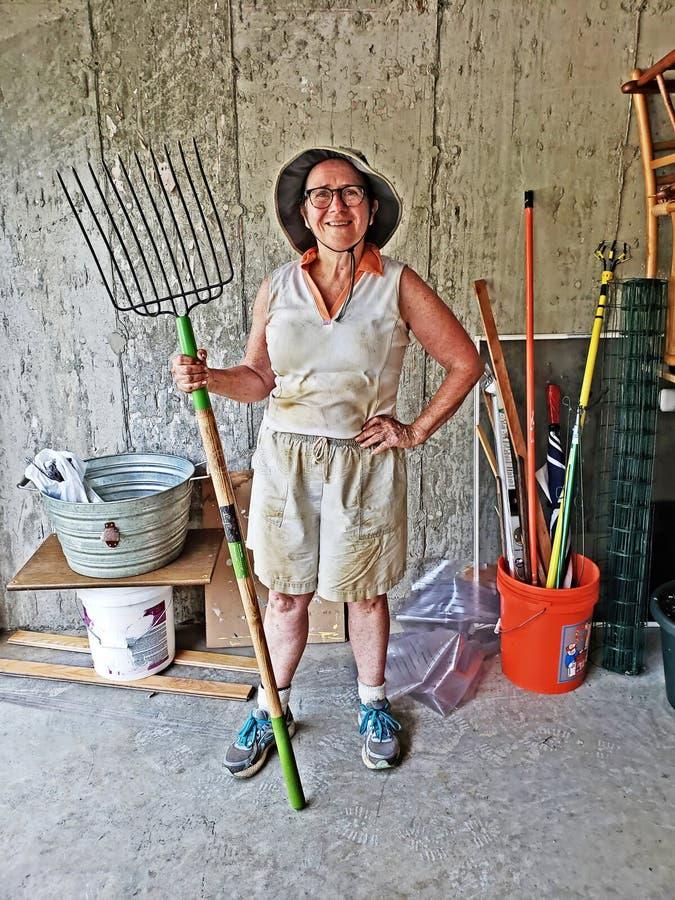 Садовник более старой женщины усмехаясь и держа вилу стоковое фото rf