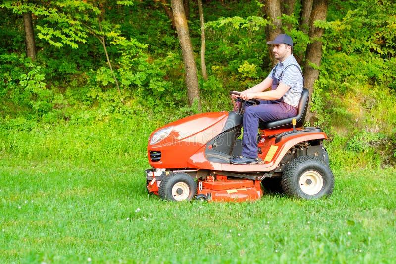 Садовник управляя травокосилкой катания в саде стоковые фотографии rf