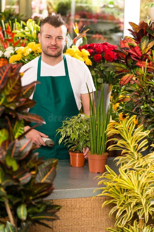 Садовничать магазина цветка штрихкода скеннирования молодого человека стоковые фотографии rf