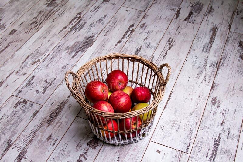 Садовничая сезон, осень и концепция плодоовощей - близкая вверх плетеной корзины с зрелыми красными яблоками на деревянном поле стоковые изображения rf