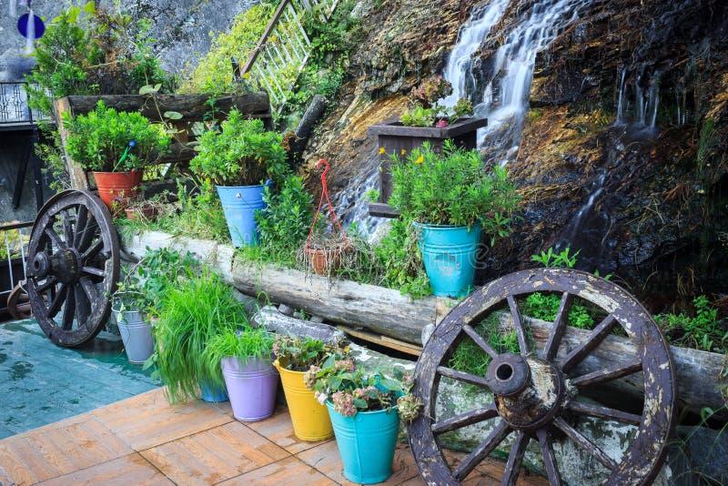 Сад с небольшим водопадом, зацветая цветками и колесами телеги стоковое изображение