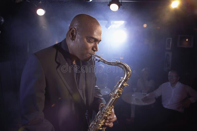 Саксофонист выполняя в джаз-клубе стоковое изображение rf