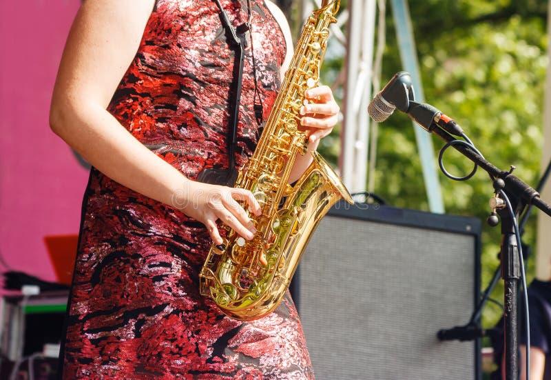 Саксофонист женщины играя на джазовом фестивале в парке города стоковое изображение rf