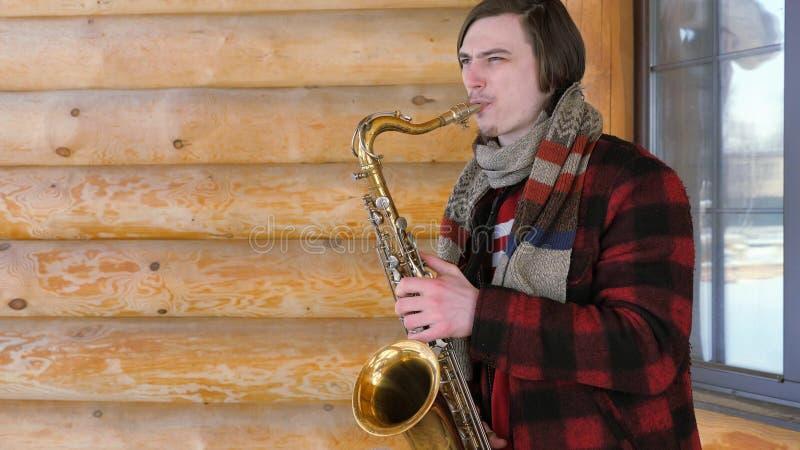 Саксофонист играет саксофон, в зиме стоковые фотографии rf