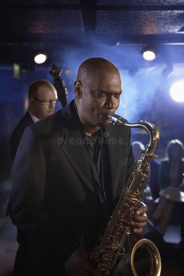 Саксофонист и двойной бас-гитарист выполняя в джаз-клубе стоковые изображения rf