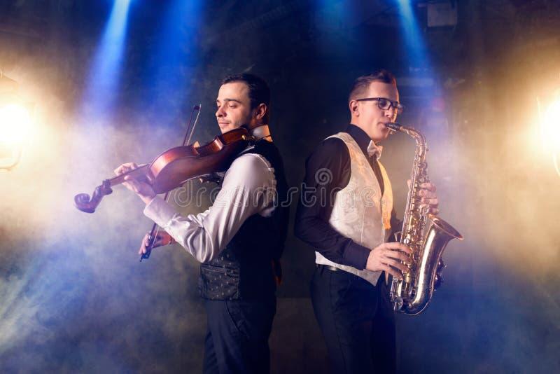 Саксофонист и скрипач играя классическую музыку стоковая фотография