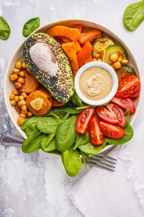 Салатница Vegan с испеченными овощами, нутами, авокадоом и t стоковые изображения rf