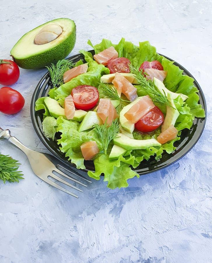 Салат авокадоа, красный овощ диеты рыб на серой конкретной предпосылке стоковые фото