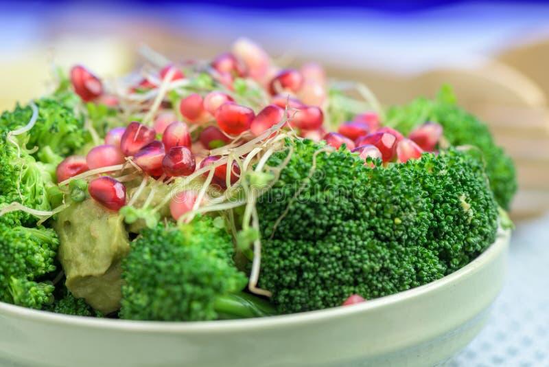 Салат брокколи с гранатовым деревом и авокадо sauce - здоровая еда vegan стоковая фотография rf