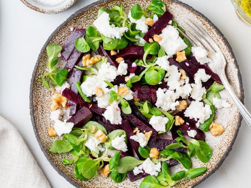 Салат бураков с фета, сыром, грецкими орехами, салатом мозоли на белом t стоковое фото