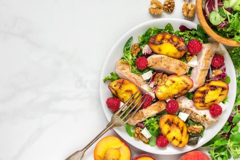 Салат витамина с зажаренными цыпленком и персиком, сыром фета, полениками и грецкими орехами в плите еда здоровая Взгляд сверху стоковые изображения