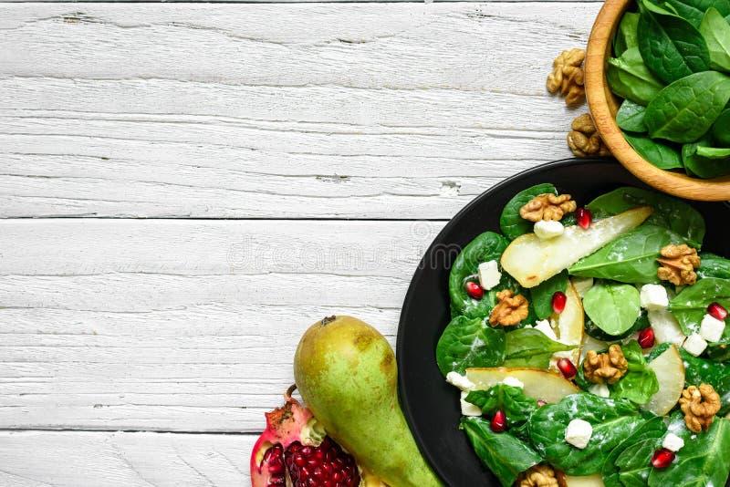 Салат витамина с сыром листьев, груши, гаек, гранатового дерева и фета шпината в черной плите стоковое изображение