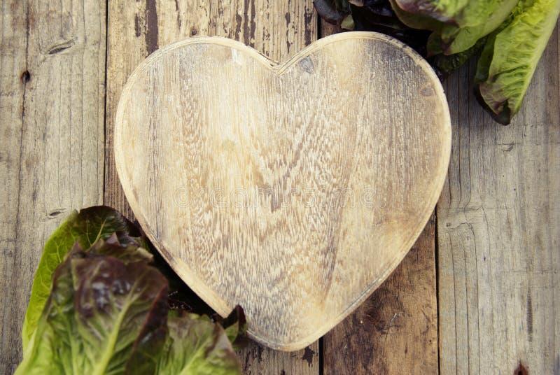 Салат выходит на форму сердца разделочной доски, на деревянной предпосылке Подготовка салата и здоровой еды Капуста салата Скопир стоковое фото