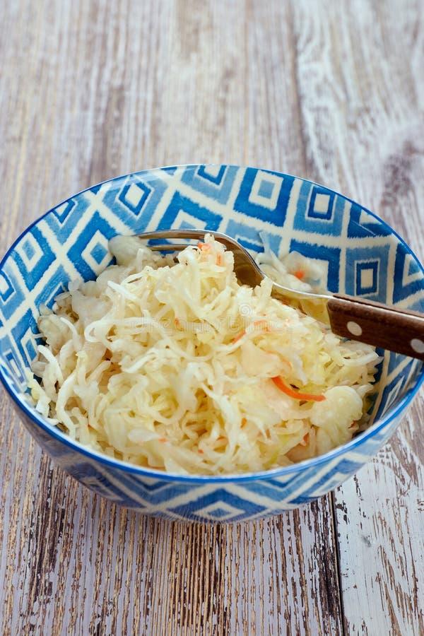 Салат замаринованной капусты Традиционный русский sauerkraut закуски с морковами в плите на белом деревянном столе стоковое изображение rf