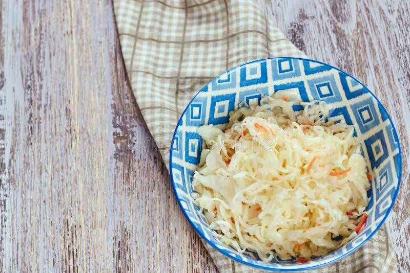 Салат замаринованной капусты Традиционный русский sauerkraut закуски с морковами в плите на белом деревянном столе стоковое фото rf