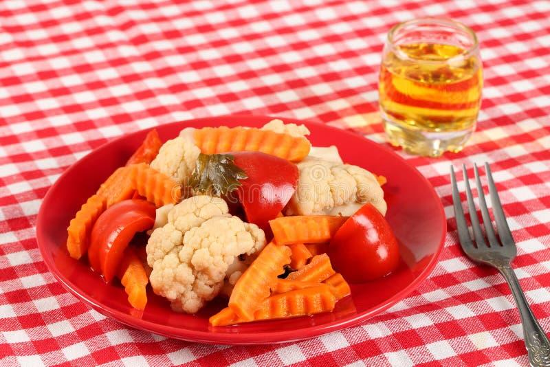Салат замаринованных кусков овощей цветной капусты, паприки и моркови в красной плите и стекле виноградины rakia, рябиновки как стоковое изображение rf