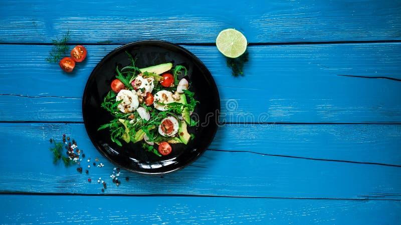 Салат из аругулы, авокадо, сыра, радужных и вишневых томатов на черной глянцевой тарелке стоковые изображения rf
