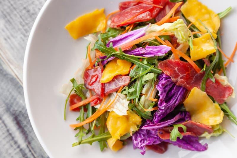Салат лета конца-вверх свежий с мясом bresaola, зелеными цветами, arugula, манго, морковью, китайской капустой Деликатес концепци стоковое фото