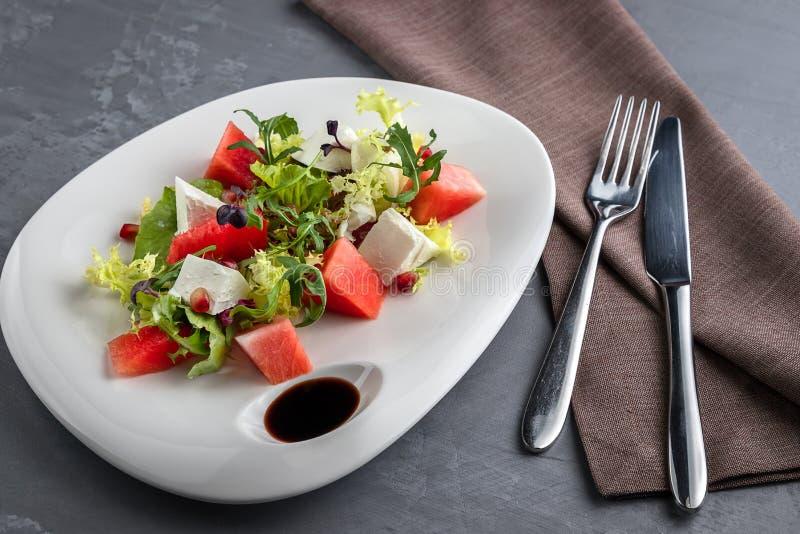 Салат лета с салатом сыра арбуза и фета в белой плите Скатерть Брауна, ложка, вилка на серой предпосылке стоковые изображения rf