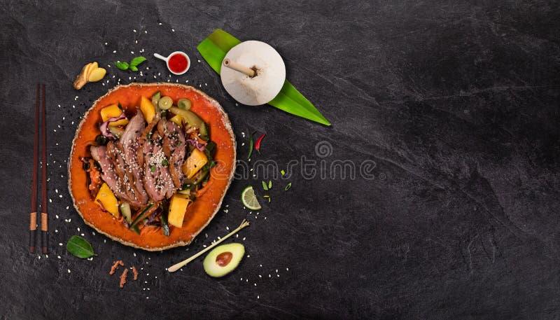 Салат манго с мясом утки на черной каменной предпосылке стоковое изображение rf