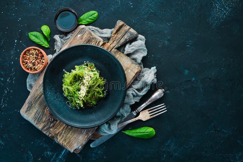 Салат морской водоросли в черной плите Wakame Chuka на старой предпосылке стоковая фотография