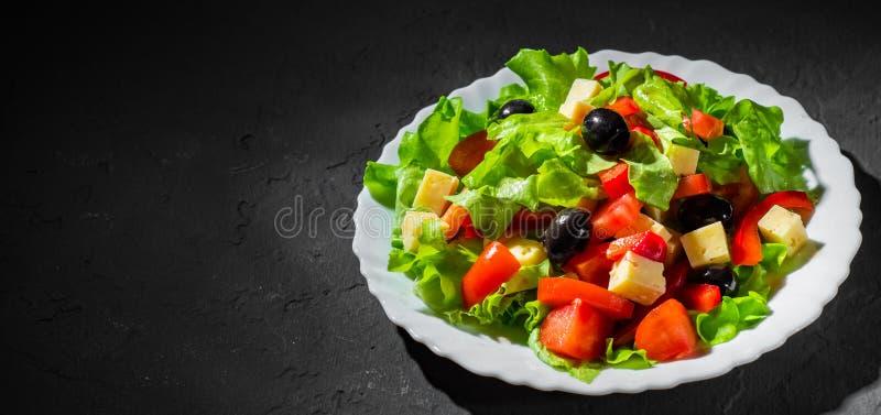 Салат овощей с салатом, оливкой, перцем, томатом и сыром в белой плите на темной черной предпосылке стоковые фотографии rf