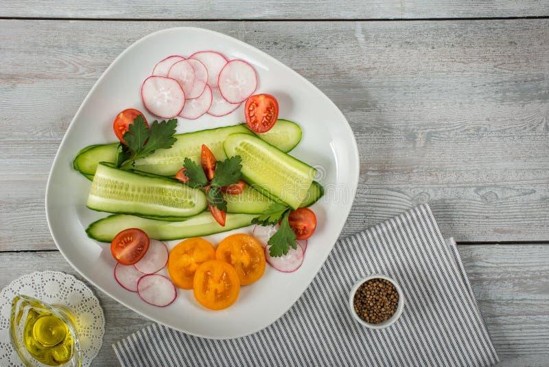 Салат огурцов и радужных блюд с помидорами на столе Высокий угол стоковое изображение rf