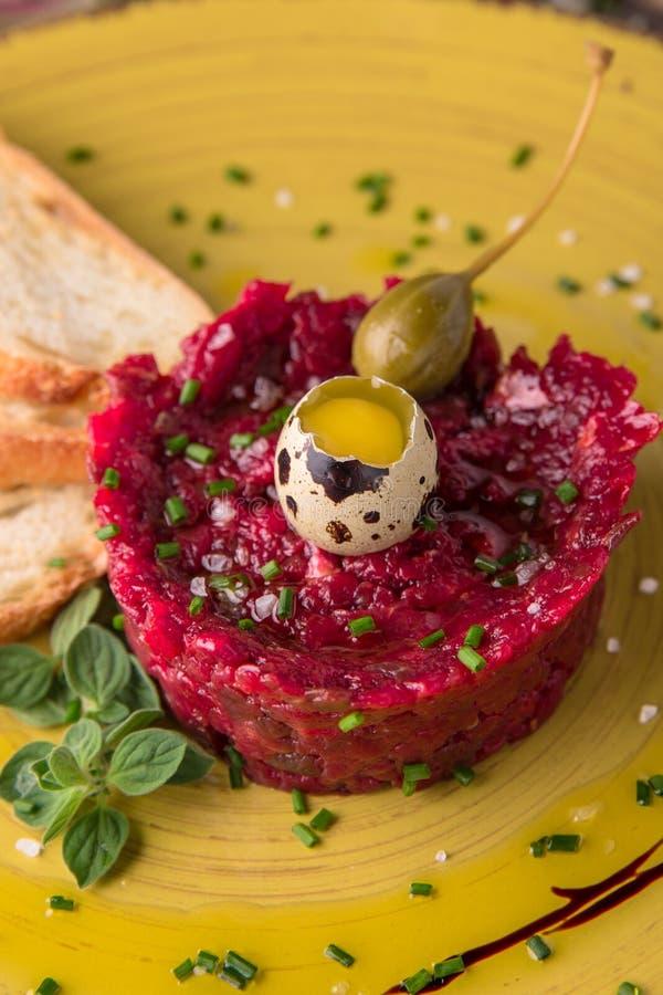 Салат от свежих свекл, яичек триперсток, marinated каперсы, зеленые цвета, украшенные с листьями валериана Красивое стильное меню стоковое фото