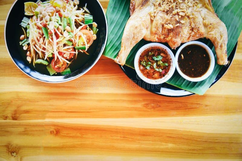 Салат папапайи и зажаренный цыпленок с соусом, который служат на плите на деревянном столе - еде тайского меню животика сома азиа стоковая фотография