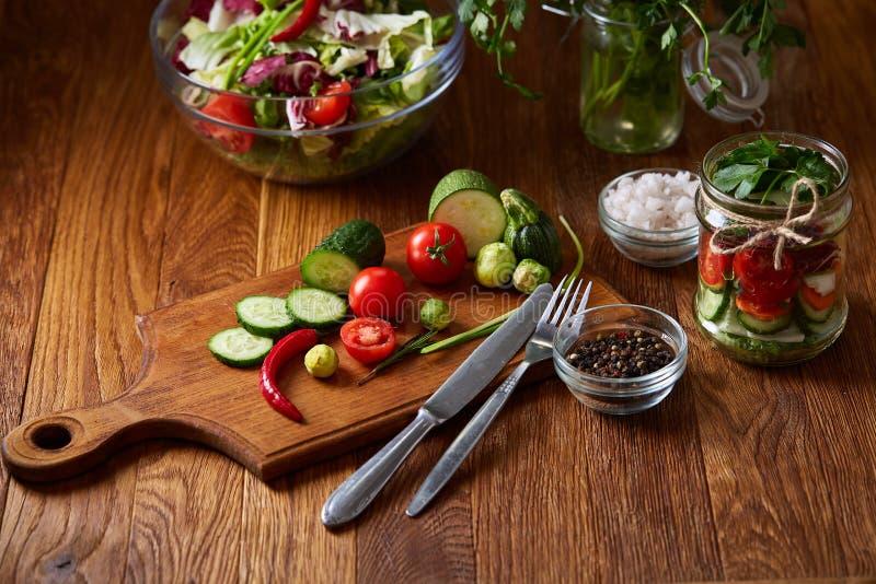 Салат свежего овоща и зрелые veggies на разделочной доске над деревянной предпосылкой, концом вверх, селективный фокус стоковое фото rf