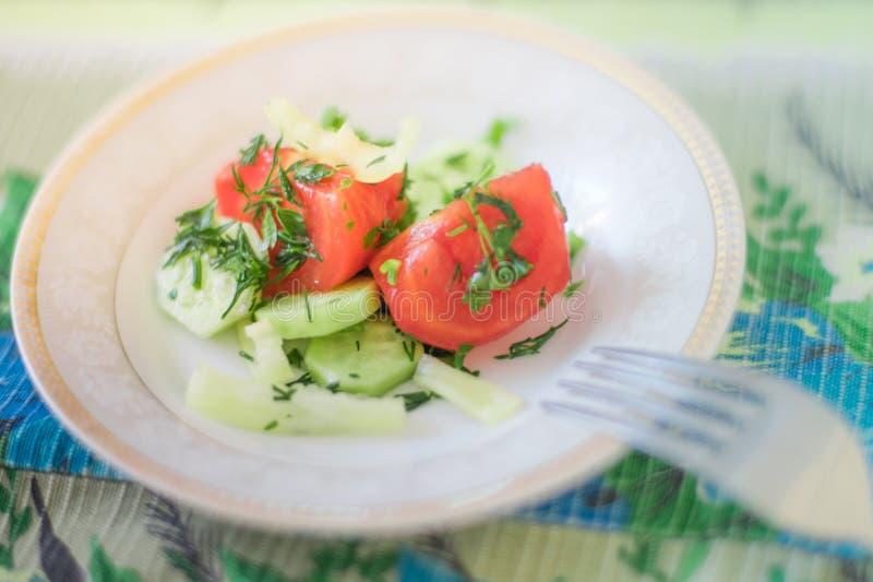 Салат со свежими томатом, огурцом, перцем и зелеными цветами на белом поддоннике с вилкой стоковое изображение