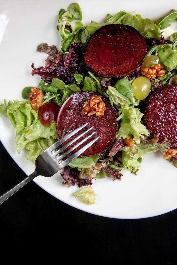 Салат стейка бураков с соусом, виноградинами и грецкими орехами голубого сыра стоковая фотография