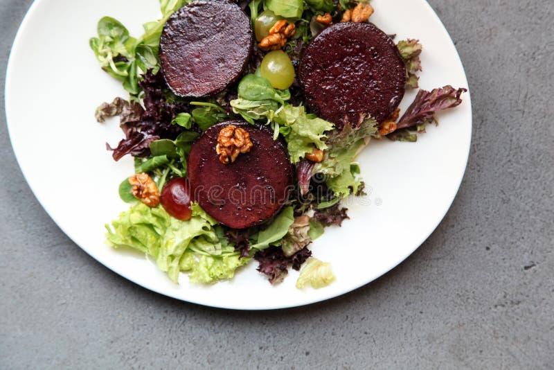 Салат стейка бураков с соусом, виноградинами и грецкими орехами голубого сыра стоковое изображение