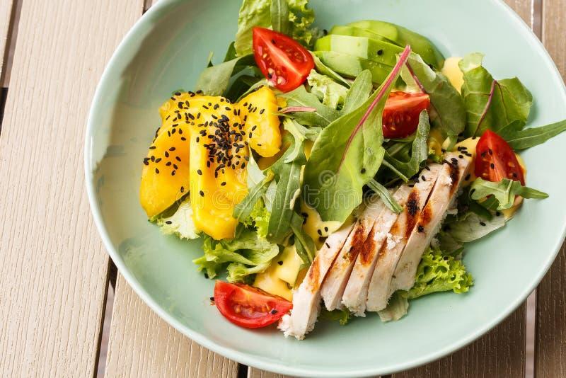 Салат с зажаренным цыпленком, манго, салатом, авокадоом, томатами, arugula, sause сыра на белой плите на деревянном стоковое фото